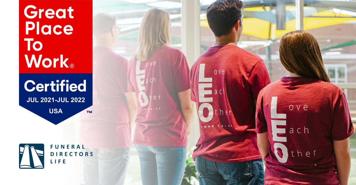"""employees standing with """"Love Each Other"""" shirts"""